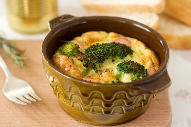 Ovos mexidos assados com brócolis, salsichas e queijo, servidos com fatias de pão. estilo rústico.