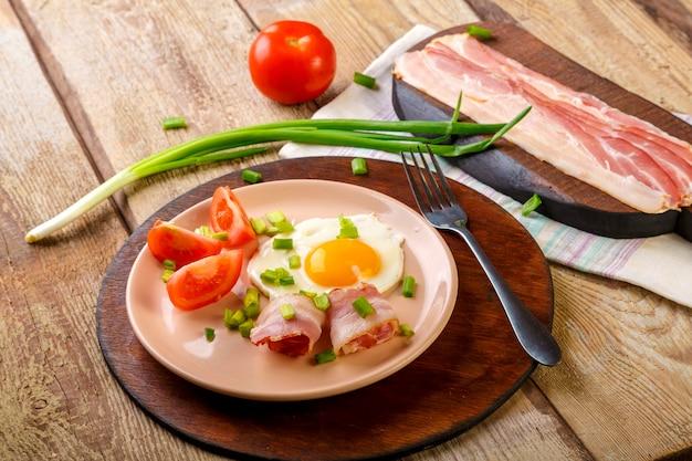 Ovos mexidos com bacon com tomate e cebolinha e em uma mesa de madeira em um prato em um suporte com um garfo ao lado de bacon e tomate picado.