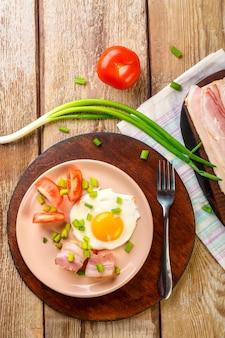 Ovos mexidos com bacon com tomate e cebolinha e sobre uma mesa de madeira em um prato com um garfo ao lado de bacon e tomate picado.