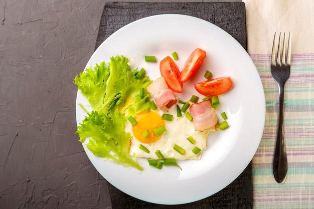 Ovos mexidos com bacon guarnecido com tomate e cebolinha e salada