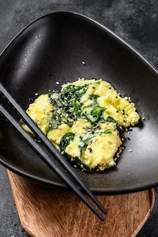 Ovos mexidos com espinafre e queijo parmesão com gergelim. fundo preto.