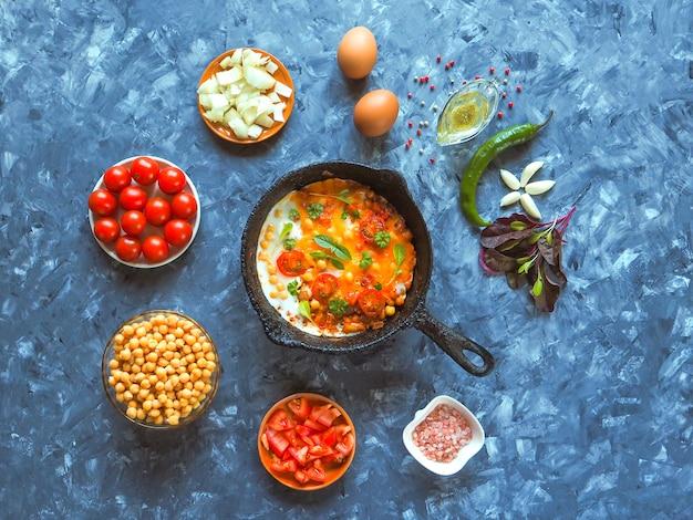 Ovos mexidos com grão de bico e tomate em uma panela velha e um conjunto de legumes.