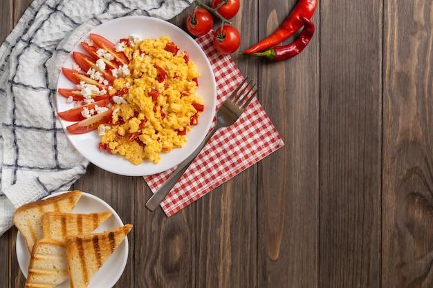 Ovos mexidos com pimenta, tomate e queijo na mesa de madeira