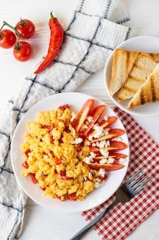 Ovos mexidos com pimenta, tomate e queijo no café da manhã.