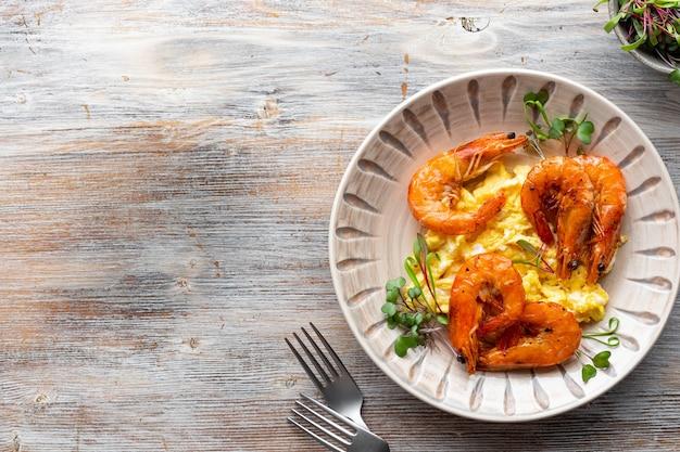 Ovos mexidos com queijo e camarões em uma mesa de madeira, copie o espaço, vista superior, postura plana.