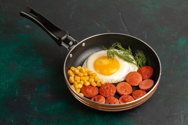 Ovos mexidos com salsichas fatiadas e verduras dentro da frigideira em superfície escura.