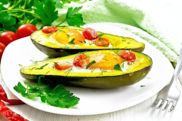 Ovos mexidos com tomate cereja em duas metades de abacate em um prato, toalha verde e garfo no fundo da placa de madeira branca