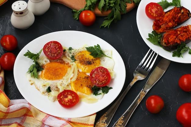 Ovos mexidos com tomate cereja estão localizados em um prato branco sobre uma superfície escura, a foto lá berinjela assada, salsa, talheres