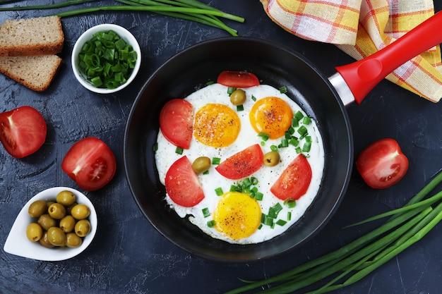 Ovos mexidos com tomate e cebola verde em uma frigideira