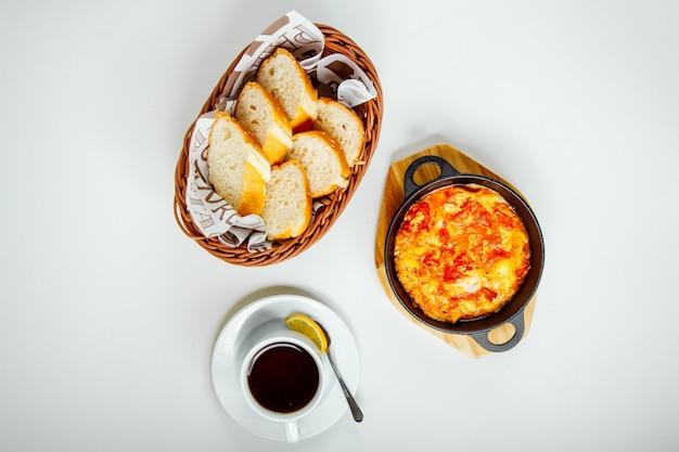 Ovos mexidos com tomate, pão e uma xícara de chá