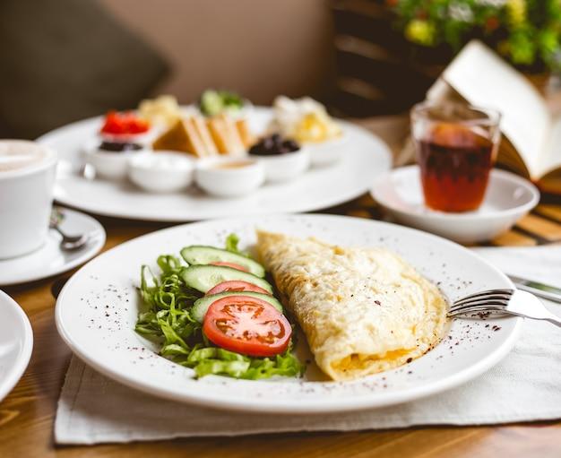 Ovos mexidos de vista frontal com fatias de tomate e pepino com ervas em um prato