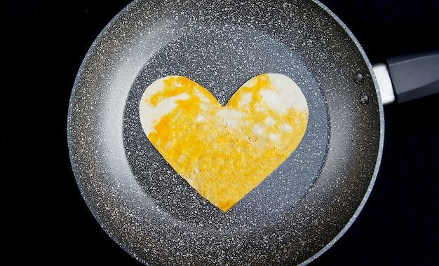 Ovos mexidos em forma de coração em uma frigideira cinza e um fundo preto