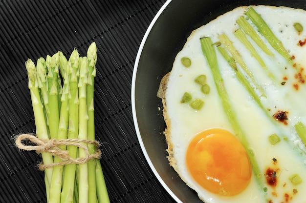 Ovos mexidos em uma frigideira com aspargos