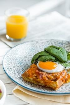 Ovos mexidos na carne com batatas fritas e torradas no prato na mesa de madeira