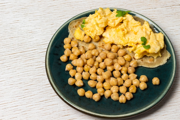 Ovos mexidos no pão pita, grão de bico cozido na placa azul.