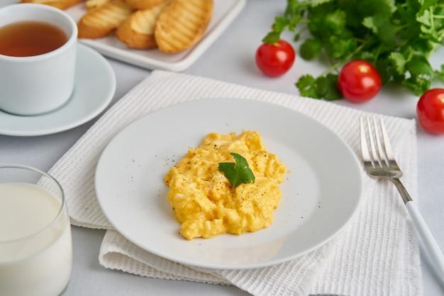 Ovos mexidos, omelete, vista lateral. café da manhã com ovos fritos, copo de leite