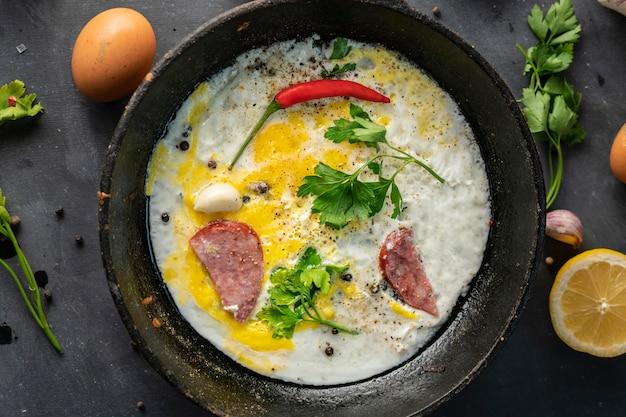 Ovos mexidos picantes ou omelete em uma frigideira com bacon, alho e pimenta, ingredientes ao redor nas mesas