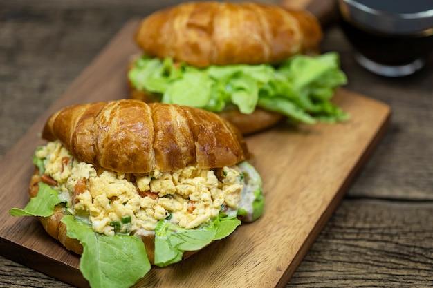 Ovos mexidos recheados de croissant na bandeja de madeira com fundo de café quente.