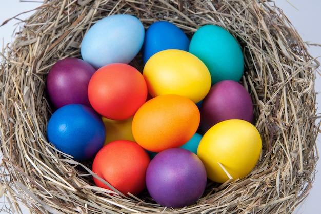 Ovos multicoloridos no ninho no feno. páscoa do conceito.