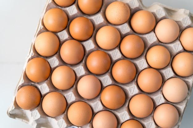 Ovos na bandeja de papel reciclado, conceito de acumulação de alimentos