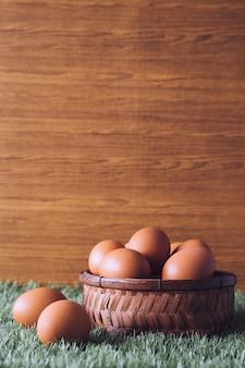 Ovos na cesta de madeira na grama verde. espaço livre para o texto