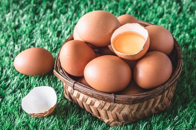 Ovos na cesta de madeira na grama verde.