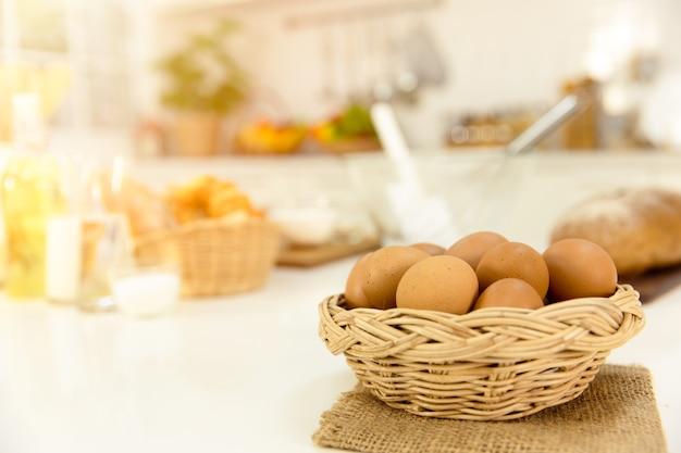 Ovos na cesta na mesa da cozinha de casa manhã dia
