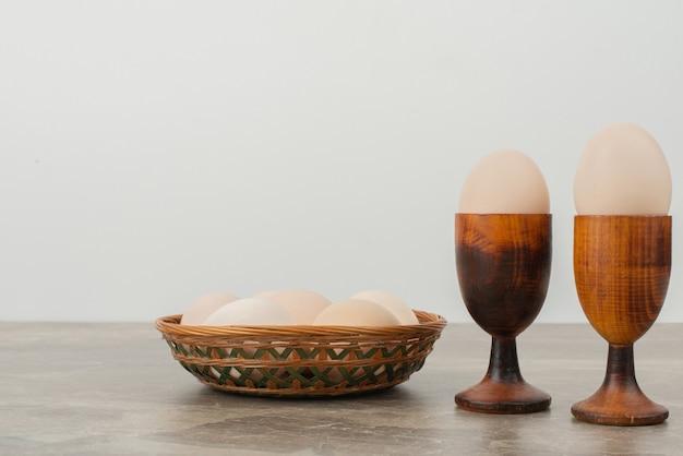 Ovos na xícara e ovos brancos na cesta.