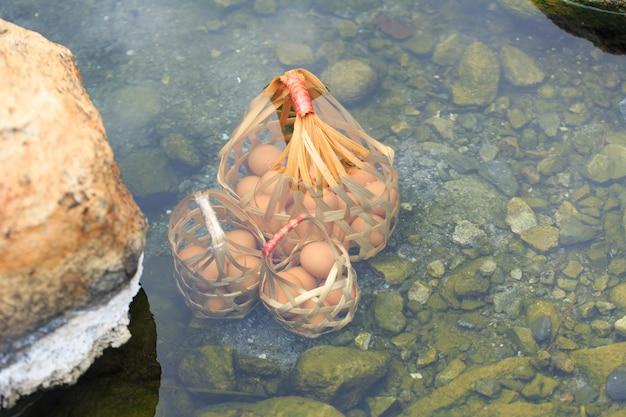 Ovos naturais da fervura para o alimento mineral, fervendo na água quente da natureza com a cesta. cozido em fontes termais.