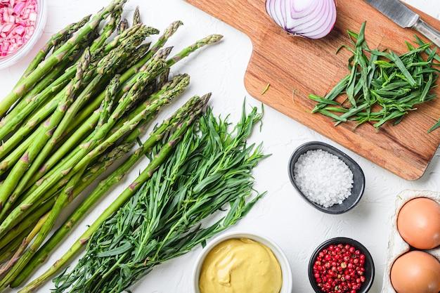 Ovos orgânicos do aspargo e ingredientes franceses do molho com mostarda de dijon, cebola desbastada no taragon do vinagre vermelho no fundo textured branco, vista superior.