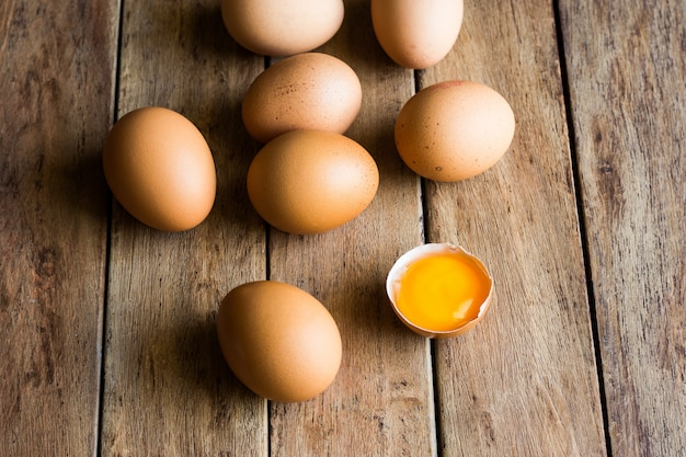 Ovos orgânicos frescos espalhados na mesa da cozinha de madeira, casca rachada com gema aberta