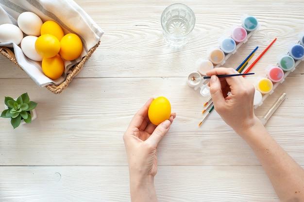 Ovos para colorir. a garota desenha padrões de tinta prateada em ovos amarelos.