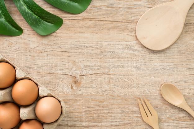 Ovos para cozinhar na vista superior de madeira.