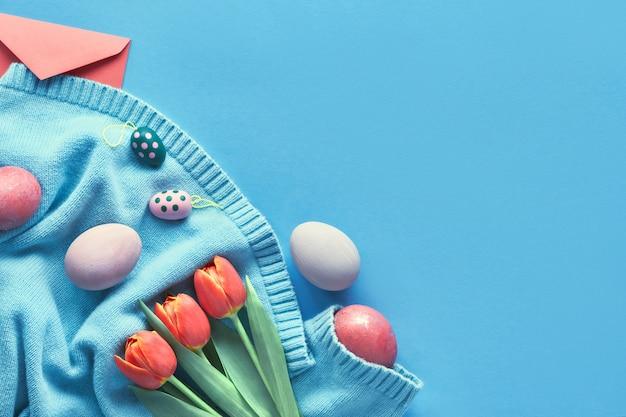 Ovos pintados, bando de tulipas laranja e envelope de saudação na camisola de algodão cor de menta, espaço de texto