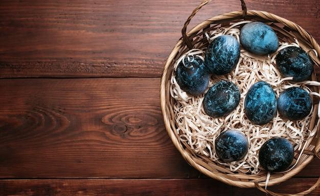 Ovos pintados com textura azul para a celebração da páscoa em uma cesta sobre um fundo de madeira