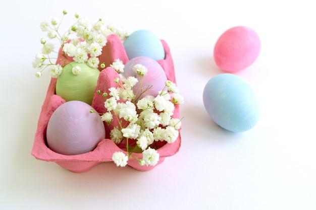 Ovos pintados cor da páscoa em um fundo branco.