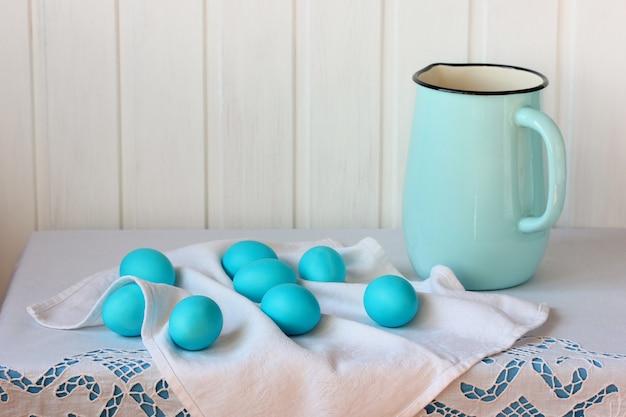 Ovos pintados de azul e um jarro esmaltado em uma mesa com uma toalha de mesa branca