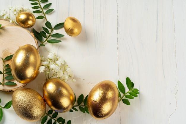 Ovos pintados dourados brilhantes com galhos florais