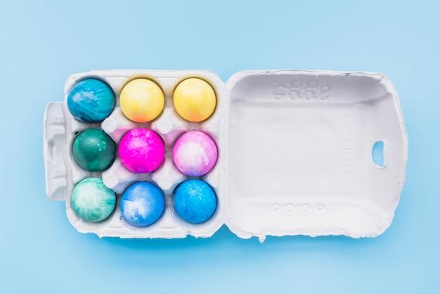 Ovos pintados em caixa de papelão no fundo azul