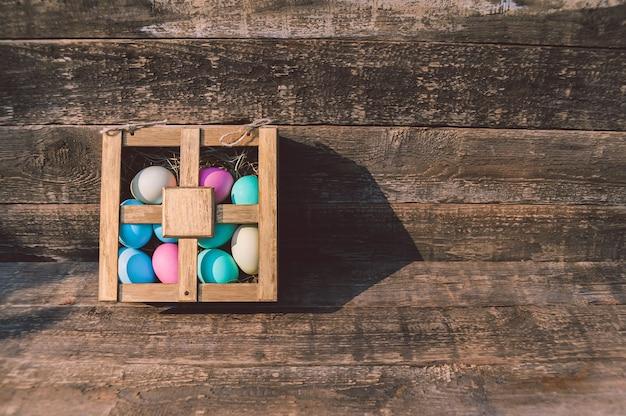 Ovos pintados em uma caixa. em cima da mesa no contexto de uma velha placa.