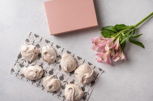 Ovos populares caseiros e sobremesa de merengue em um papel de confeitaria em uma superfície clara ao lado da flor rosa e da caixa de presente