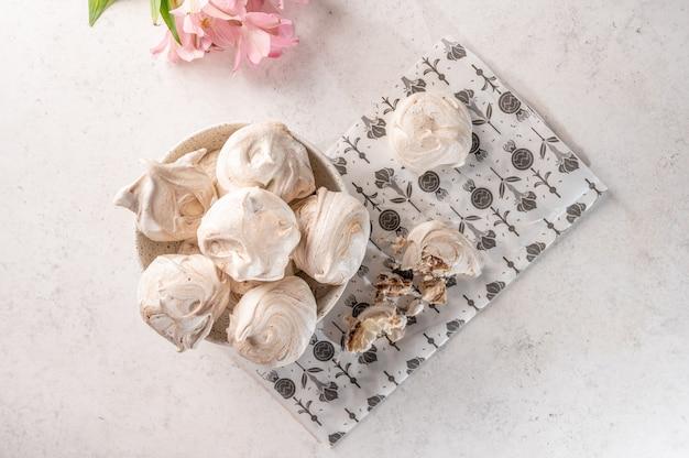 Ovos populares caseiros e sobremesa de merengue em um prato sobre um papel de confeitaria em uma superfície clara
