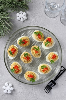 Ovos recheados com atum e queijo decorado caviar vermelho, lanche festivo em fundo cinza claro.