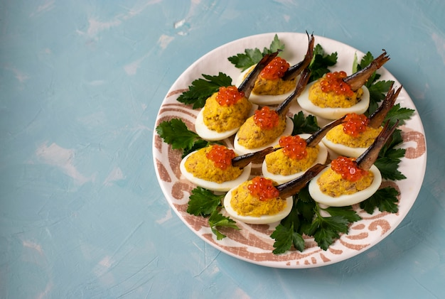 Ovos recheados com espadilhas e caviar vermelho em um prato sobre fundo azul.