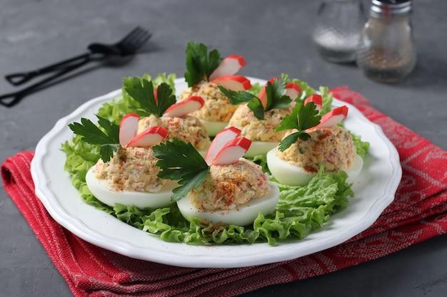 Ovos recheados com palitos de caranguejo e queijo, um delicioso lanche festivo em fundo escuro. fechar-se.