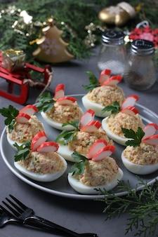 Ovos recheados com palitos de caranguejo, um delicioso lanche festivo. fechar-se. composição de natal.