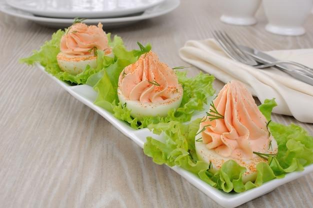 Ovos recheados com patê de salmão com pimenta vermelha em folhas de alface