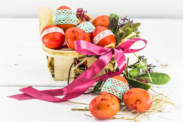 Ovos vermelhos amarrados com fita de renda, em uma cesta de páscoa com um laço