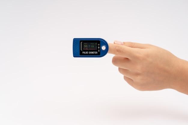 Oxímetro de pulso da ponta do dedo no dedo. sobre fundo branco. dispositivo para autodiagnóstico de saúde.