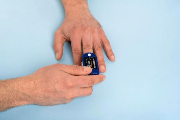 Oxímetro de pulso de mão humana usado para medir a taxa de pulso e os níveis de oxigênio com fundo azul médico com espaço de cópia.